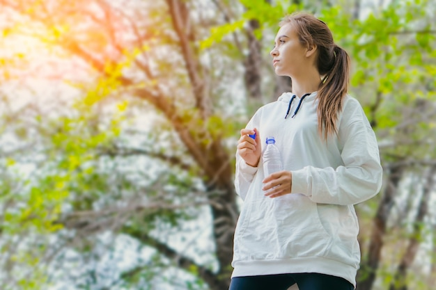 Young caucasian girl drinking water in park while jogging. copy space