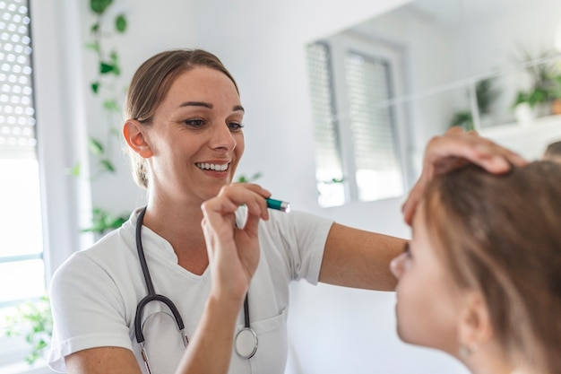 目の検査を受ける白人の少女。フォロプターデバイスで小さな女性患者の視力を調べる女性眼鏡技師のクローズアップ側面図。