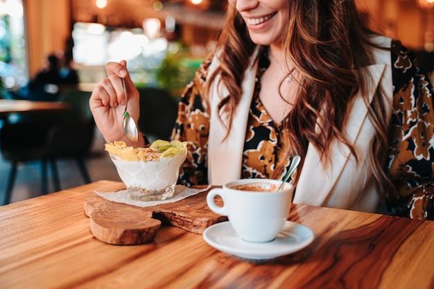 レストランで彼女の食事療法のために健康的な朝食を食べている若い白人の女の子。