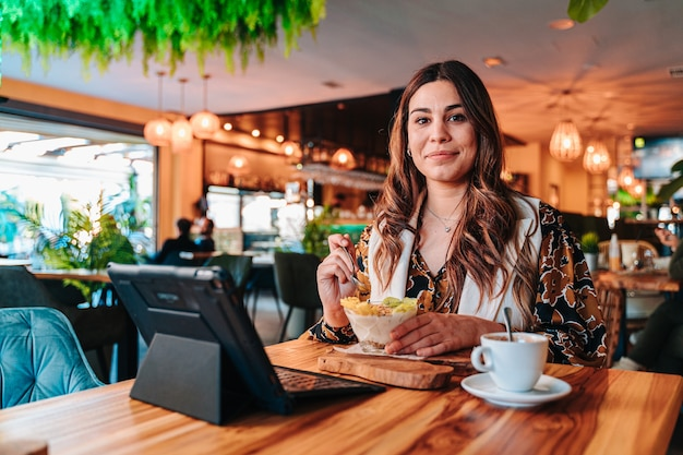 Young caucasian girl having a healthy breakfast for her diet in a restaurant.