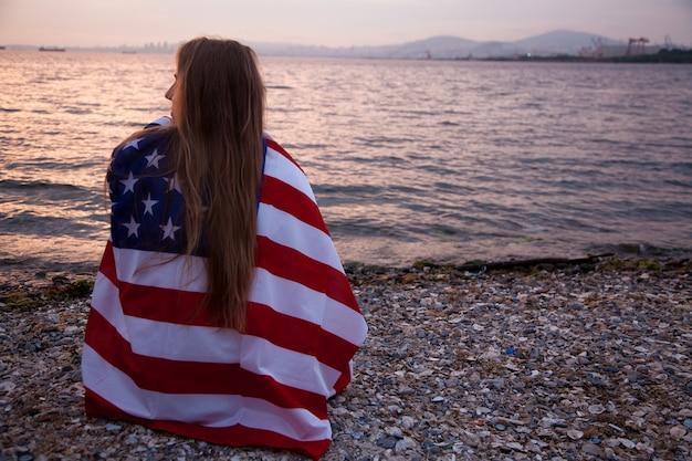 Молодая кавказская девушка держит американский флаг в руках, сидя на пляже