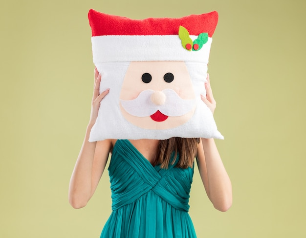 彼女の顔の前にサンタの枕を保持している若い白人の女の子