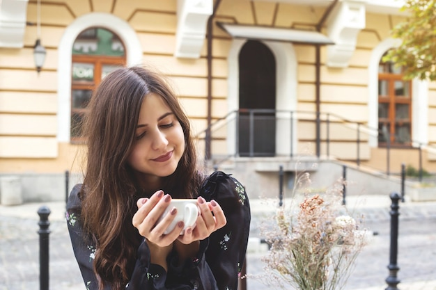 A young caucasian girl holds in her hands and looks at a cup of coffee in outdoors cafe.