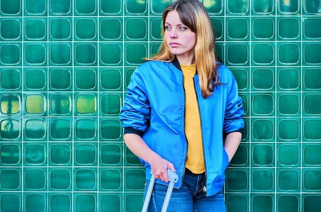 スーツケースと緑の壁に寄りかかって待っている青いジャケットの若い白人の女の子