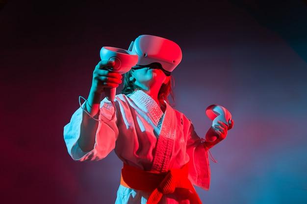 仮想現実でビデオ ゲームをする空手の制服を着た若い白人の女の子