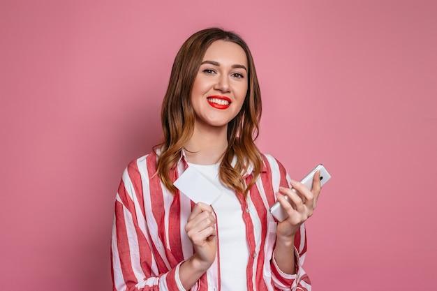 ピンクのスタジオの背景に分離された手で携帯電話とクレジットカードを笑顔で保持している縞模様のシャツの若い白人の女の子