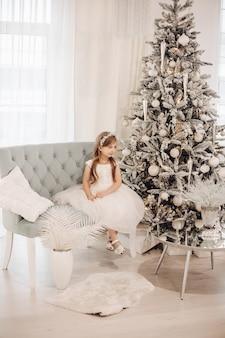 흰 드레스에 젊은 백인 여자는 크리스마스 분위기에서 카메라에 포즈