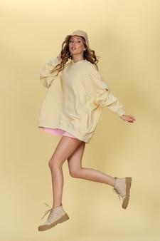 黄色の背景に長い黄色のパーカーとサファリ帽子でジャンプする若い白人の女の子