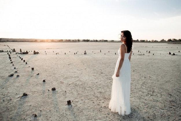 Young caucasian girl in long white dress without sleeves is looking through the shoulder in the evening on the sandy area