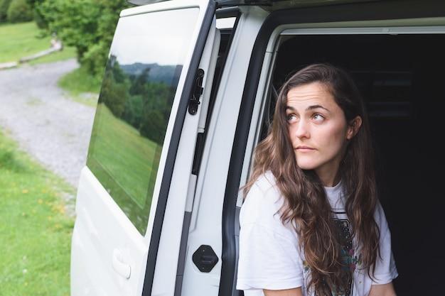 Молодая кавказская девушка смотрит на горный пейзаж из автофургона