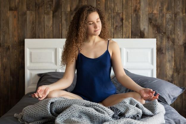 젊은 백인 소녀는 아침에 그의 방에 있는 침대에서 명상을 한다