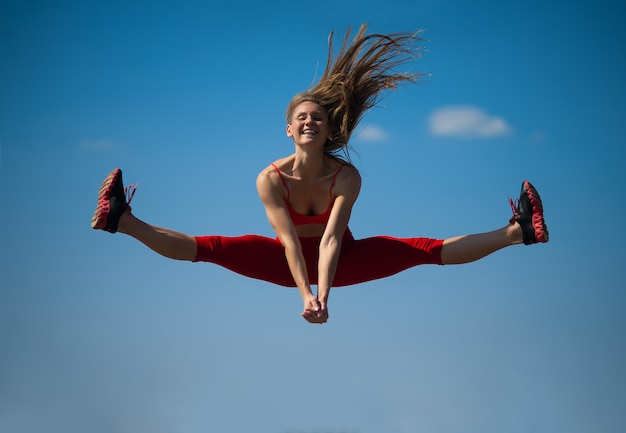 Young caucasian girl performs twine jumping on sky backround.