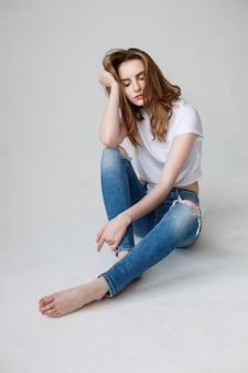 若い白人の女の子がtシャツ、破れたジーンズ、スタジオの床に座ってポーズ