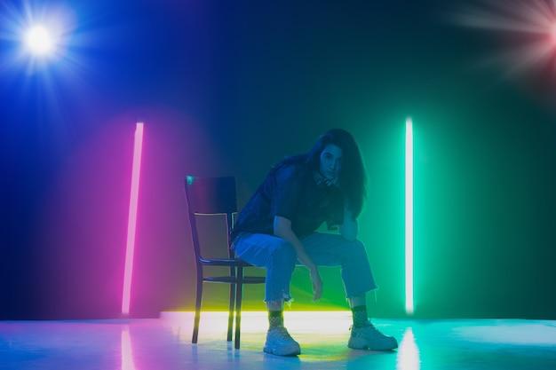 Young caucasian girl posing stylish in neon light on dark background