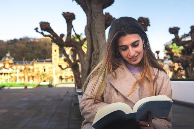 Donostia-san sebastian basque country의 거리에서 벤치에서 책을 읽는 어린 백인 소녀.