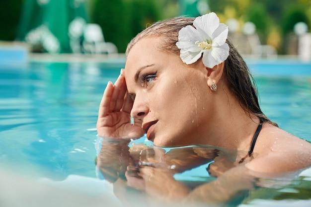 Young caucasian girl relaxing in swimming pool at spa resort