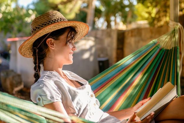 Молодая кавказская девушка сидит на гамаке в саду и читает книгу