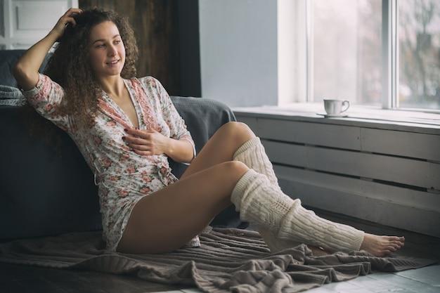 バスローブと暖かい靴下を着てベッドの近くの床に座っている若い白人の女の子