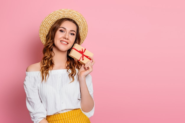 A young caucasian girl in a straw hat white dress smiles and holds a craft gift box with a red ribbon on a pink wall . happy girl hugs a box with a present