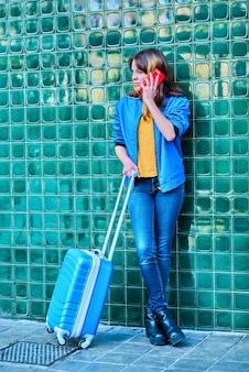 Молодая кавказская девушка разговаривает по телефону на улице, прислонившись к зеленой стене с чемоданом