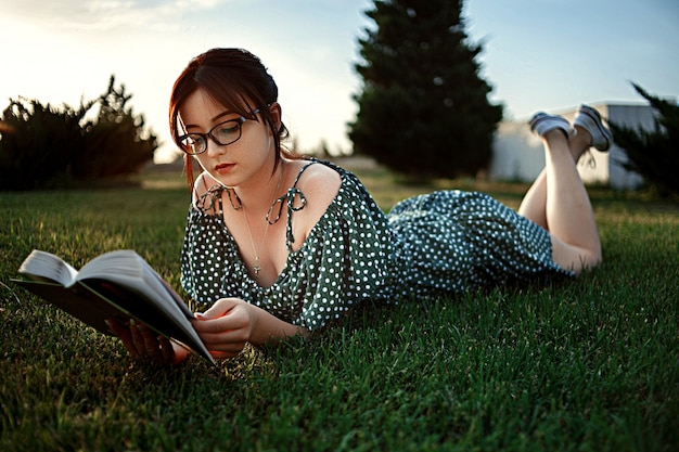 Young caucasian girl in vintage retro dress reads a book on the lawn during sunset
