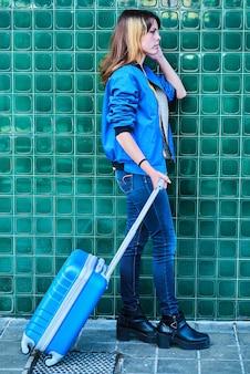 Молодая кавказская девушка идет по улице с синим чемоданом