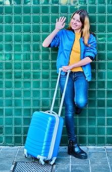 Молодая кавказская девушка машет другому человеку, прислонившись к зеленой стене с синим чемоданом на колесиках