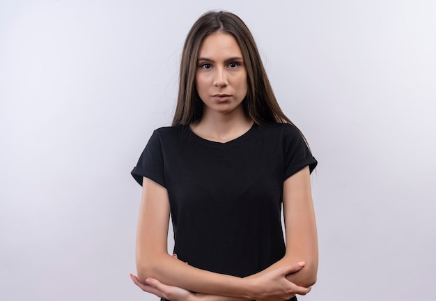 Молодая кавказская девушка в черной футболке, скрестив руки на изолированной белой стене