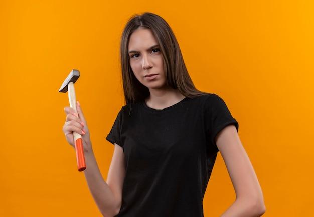 Молодая кавказская девушка в черной футболке держит молоток на изолированной оранжевой стене