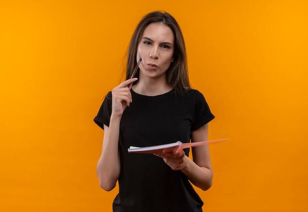 ノートブックを保持している黒いtシャツを着ている若い白人の女の子は、孤立したオレンジ色の壁の頬にペンを置きます