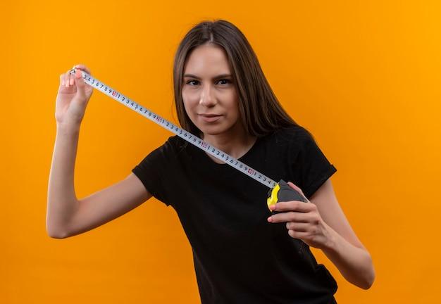 Giovane ragazza caucasica che indossa la maglietta nera che tiene la misura di nastro sulla parete arancione isolata