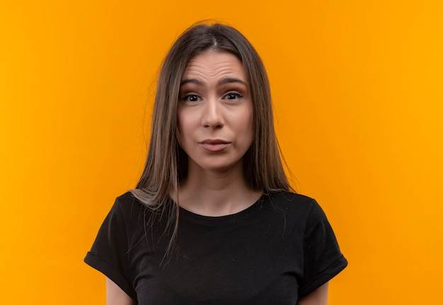 Young caucasian girl wearing black t-shirt on isolated orange wall