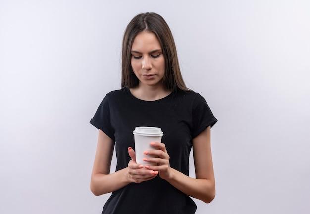 孤立した白で彼女の手にコーヒーのカップを見て黒いtシャツを着ている若い白人の女の子