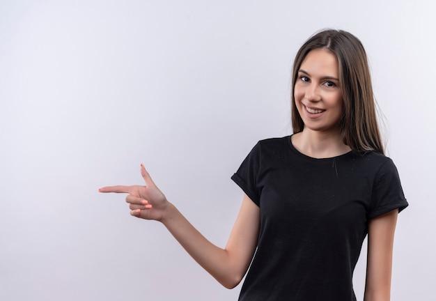 Молодая кавказская девушка в черной футболке указывает в сторону на изолированной белой стене