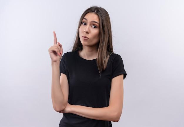 Молодая кавказская девушка в черной футболке указывает пальцем на изолированную белую стену