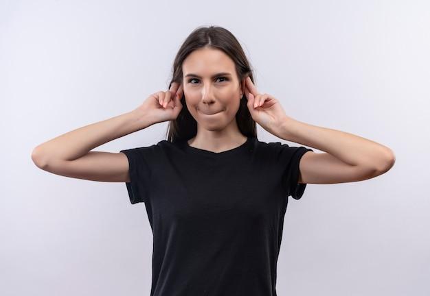 Giovane ragazza caucasica che indossa la maglietta nera mise le dita intorno alle orecchie sul muro bianco isolato