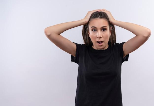 Giovane ragazza caucasica che indossa la maglietta nera mise le mani sulla testa sul muro bianco isolato