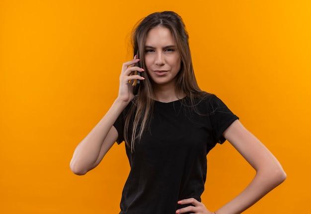 Giovane ragazza caucasica che indossa la maglietta nera parla al telefono mise la mano sul fianco sul muro arancione isolato