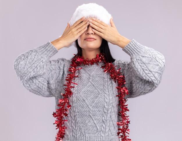 흰 벽에 고립 된 손으로 눈을 덮고 목 주위에 크리스마스 모자와 반짝이 갈 랜드를 입고 젊은 백인 여자
