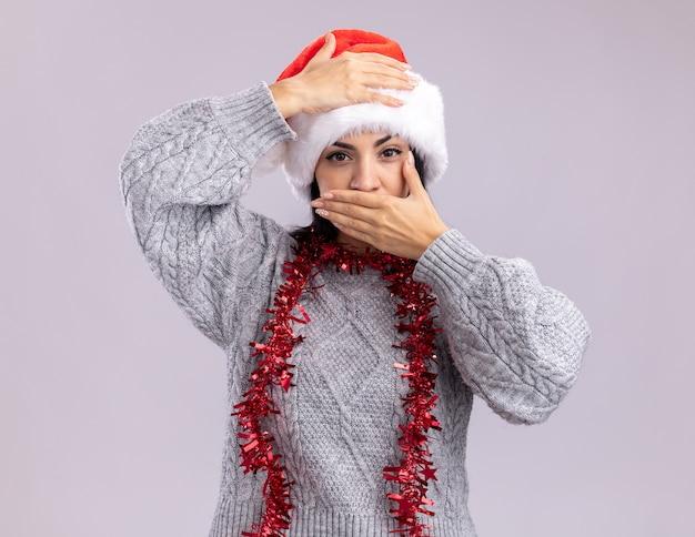 크리스마스 모자와 틴 셀 화환을 입고 젊은 백인 여자 머리와 흰 벽에 고립 된 입에 손을 유지 목