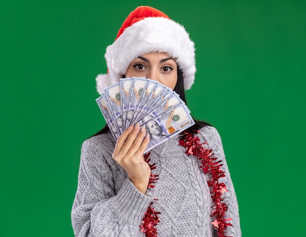 Young caucasian girl wearing christmas hat and tinsel garland around neck holding money looking at camera from behind it isolated on green background