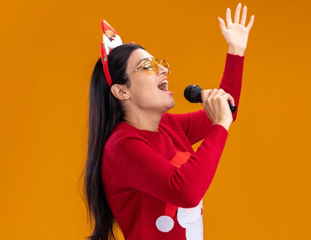サンタクロースのカチューシャとセーターを着た若い白人の女の子が横顔ビューに立って口の近くにマイクを持ち、目を閉じて歌う、コピースペースのあるオレンジ色の壁に手を上げている