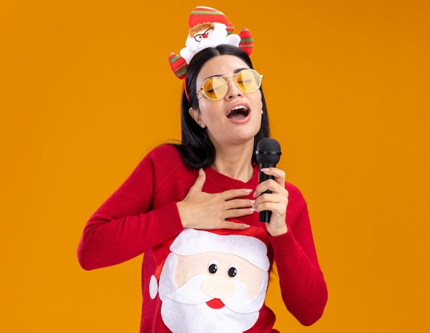 Giovane ragazza caucasica che indossa la fascia e il maglione di babbo natale con gli occhiali che tengono il microfono vicino alla bocca cantando con gli occhi chiusi tenendo la mano sul petto isolata sulla parete arancione con spazio per le copie
