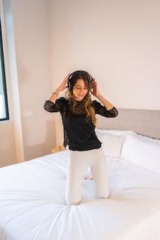 ベッドの上で踊り、音楽を楽しんでいるヘッドフォンを持つ若い白人の女の子
