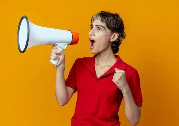 Giovane ragazza caucasica con taglio di capelli pixie pugno di serraggio parlando da altoparlante guardando lato isolato su sfondo arancione