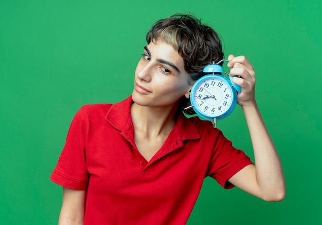 Молодая кавказская девушка с прической пикси держит будильник, глядя вниз на зеленом фоне