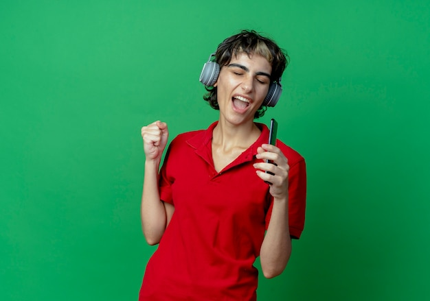 Young caucasian girl with pixie haircut wearing headphones listening to music holding mobile phone pretend singing using phone as microphone with clenched fist and closed eyes