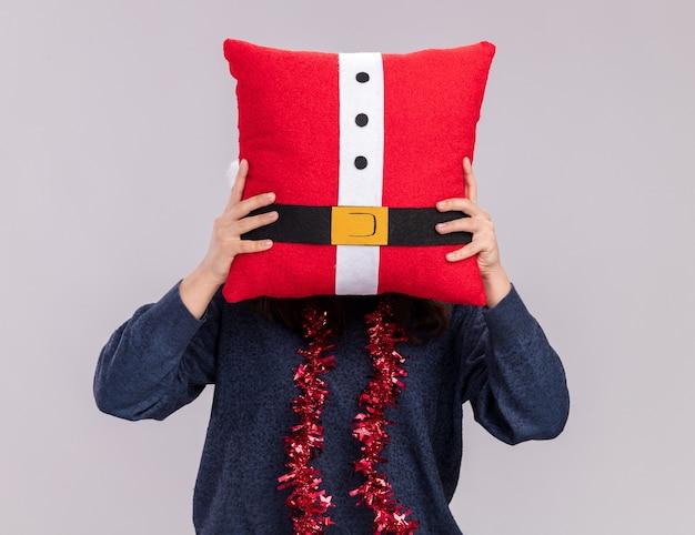 Giovane ragazza caucasica con santa cappello e ghirlanda intorno al collo tiene cuscino decorato davanti alla sua testa isolato su sfondo bianco con copia spazio