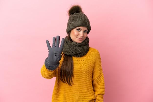 Молодая кавказская девушка в зимней шапке изолирована на розовом фоне счастлива и считает четыре пальцами