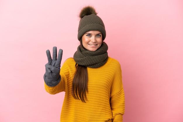 幸せなピンクの背景に分離された冬の帽子と指で3を数える若い白人の女の子